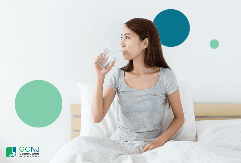 woman in bed drinking water