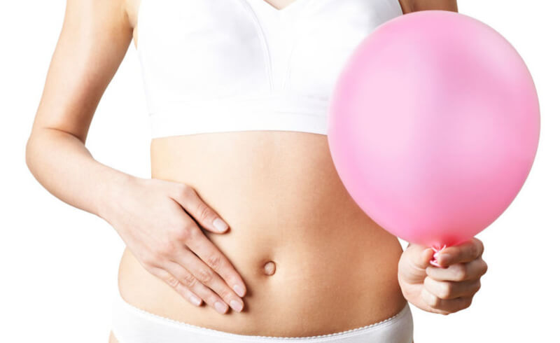 woman touching her belly and holding a pink ballon