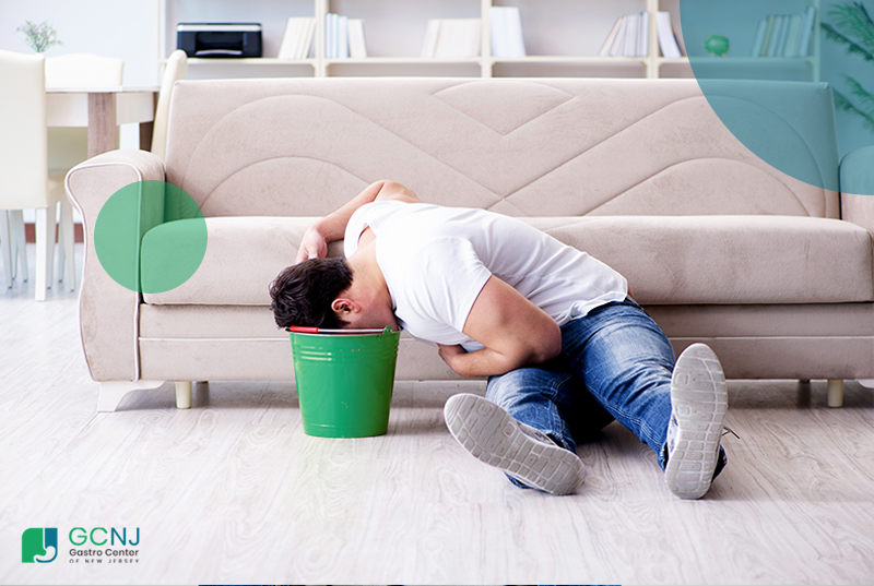 man throwing up in a bucket near the couch