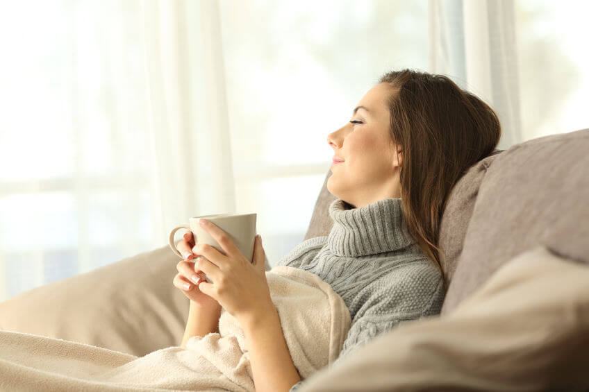 woman sitting on the sofa and drinking tea